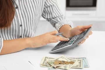 Woman counting taxes at table, closeup