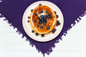 Christmas pancakes with honey and blueberries on a violet napkin