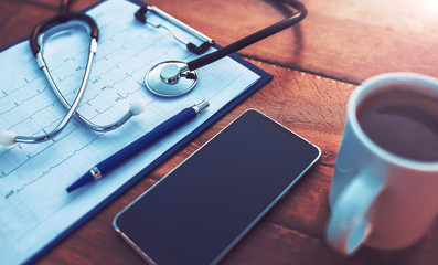 Doctor workplace. Stethoscope with notebook and pencil on the wooden table. Medical concept