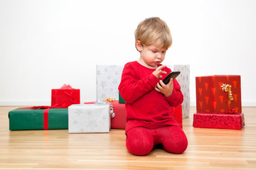 Happy Christmas  Cute Toddler Series with Gifts and Tree in his Modern Home with wooden floor and white walls: writing wish list on Smart Phone