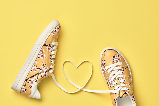 Fashion Trendy Trainers with Heart. Love, Hipster Set. Pastel Color. Minimal Style. Summer Yellow Floral Sneakers. Flat lay. Spring Girl. Art Design. Valentines day