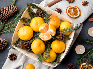 Fresh mandarins in a wooden basket with fir tree branches, star anise cinnamon on gray background