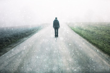 Man standing alone on rural foggy and misty asphalt road at snowy day.