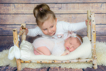 Happy child girl with Newborn sister sleeping on the tiny bed