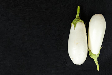 White eggplant on a black stone surface with water drops. Top view. Copy space.