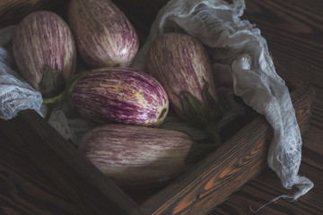 Purple graffiti eggplants, onion and Purple graffiti eggplants in a wooden box in a vintage wooden background in rustic style, selective focus. Tonedbasil. Toned