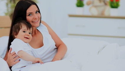 mother and baby in diaper playing in sunny bedroom
