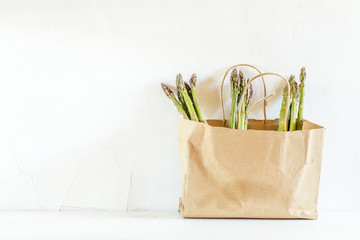 Bunches of fresh asparagus in a paper bag on white cracked wall background. Copy space