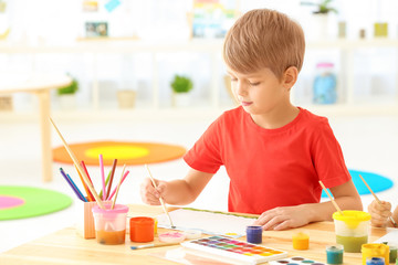 Cute boy painting picture at table indoors