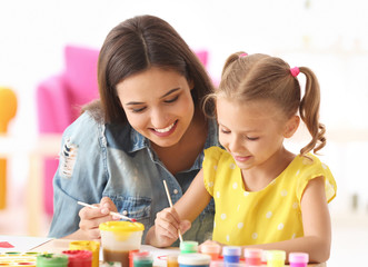 Cute girl with mother painting at table indoors