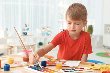 Talented boy painting at table in room