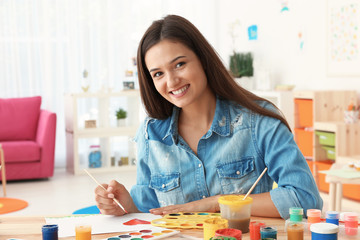 Beautiful young woman painting heart at table in room