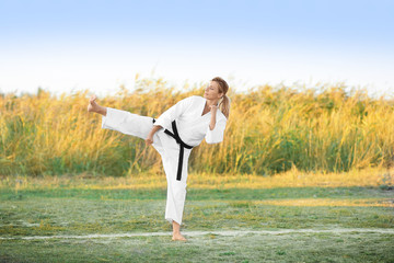 Young woman practicing karate outdoors