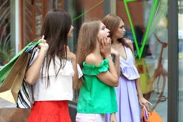 Young women with shopping bags looking at showcase of store
