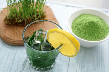 Glass of wheat grass juice with lemon on wooden table