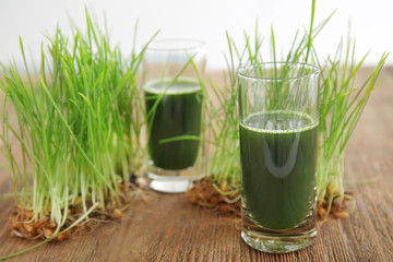 Shots of healthy juice and sprouted wheat grass on wooden table
