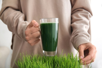 Woman holding glass cup of fresh juice over sprouted wheat grass, close up