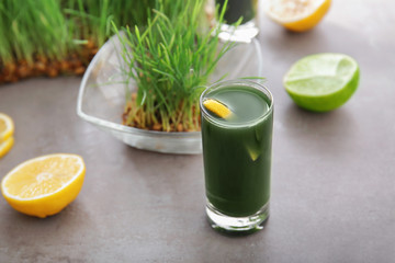 Shot of healthy juice and sprouted wheat grass on table