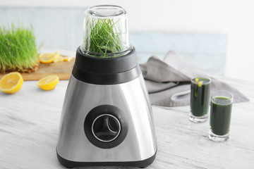 Blender with wheat grass on table