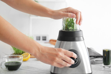 Woman making wheat grass juice with blender on table
