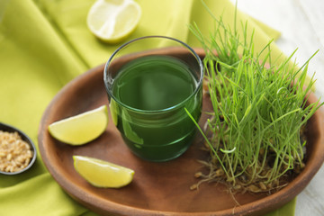 Plate with glass of wheat grass juice on table