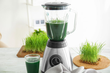 Blender with wheat grass juice on table