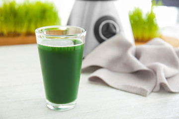 Glass of wheat grass juice on table