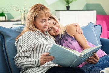 Mature woman and her daughter with photobook at home