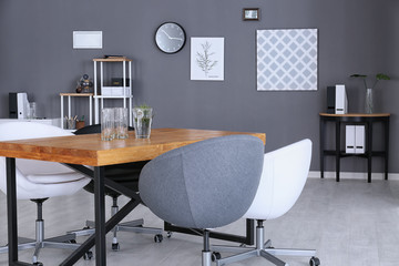 Modern office interior with wooden table and armchairs