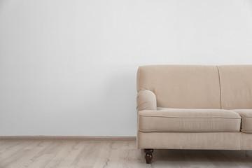 Stylish sofa on white wall background