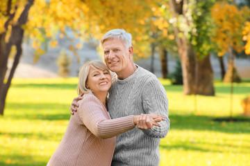 Cute elderly couple dancing in autumn park
