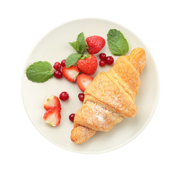Plate with delicious croissant and berries on white background