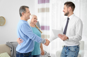 Male insurance agent with clients in office