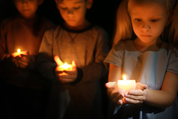 Little children holding burning candles in darkness