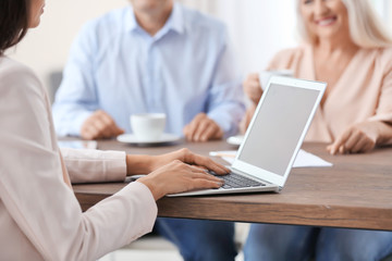 Female insurance agent consulting clients in office
