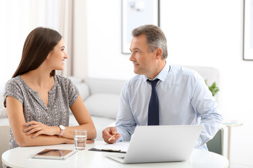 Male insurance agent consulting young woman in office