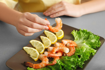 Woman holding tasty shrimp over plate on table