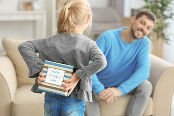 Cute girl hiding present for father behind her back