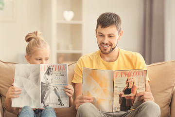 Cute little girl and her father reading magazines at home