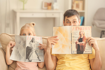Funny little girl and her father with magazines at home