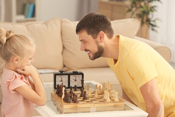 Cute girl playing chess with her father at home