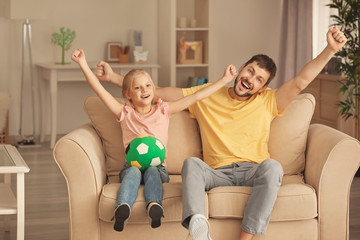 Cute girl and her father watching football match on TV