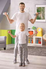 Cute girl and her father training with dumbbells at home