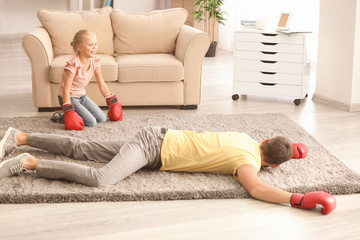 Cute girl and her father in boxing gloves playing at home