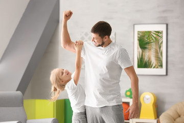 Cute little girl and her father playing at home