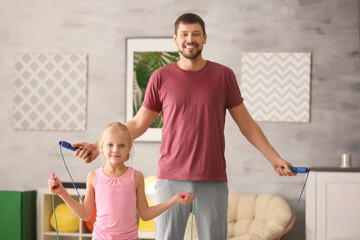 Cute girl and her father jumping rope at home