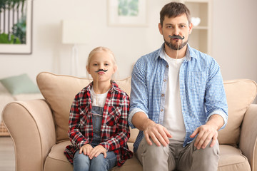 Cute little girl and her father with mustaches on sticks at home