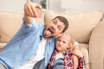 Cute little girl and her father taking funny selfie at home