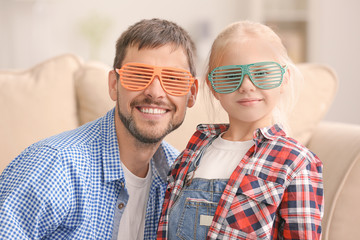 Cute little girl and her father wearing party sunglasses at home
