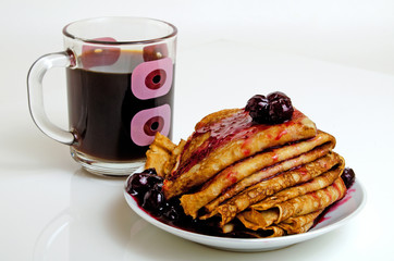 Pancakes with cherry jam and coffee.